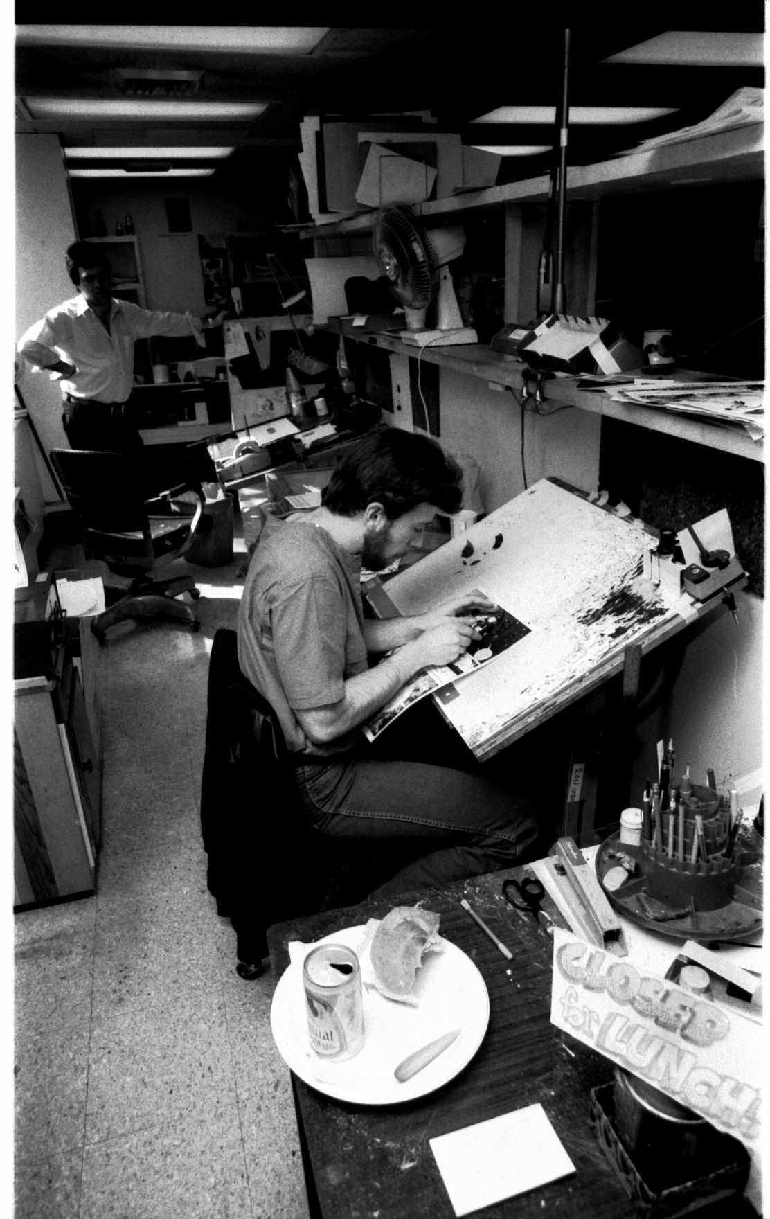 Work never stopped! Despite a small party, artist Bill Sienkiewicz uses Ron Zalme's desk to do some quick fixes. Robbie Carosella looks on.