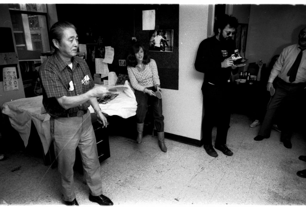 Morrie Kuramoto displaying the cool, calm collection that made him famous in the Marvel Bullpen. Rick Parker-- the Man in Black-- is holding a Polaroid instant print camera, but is not using it as those shots are expensive.