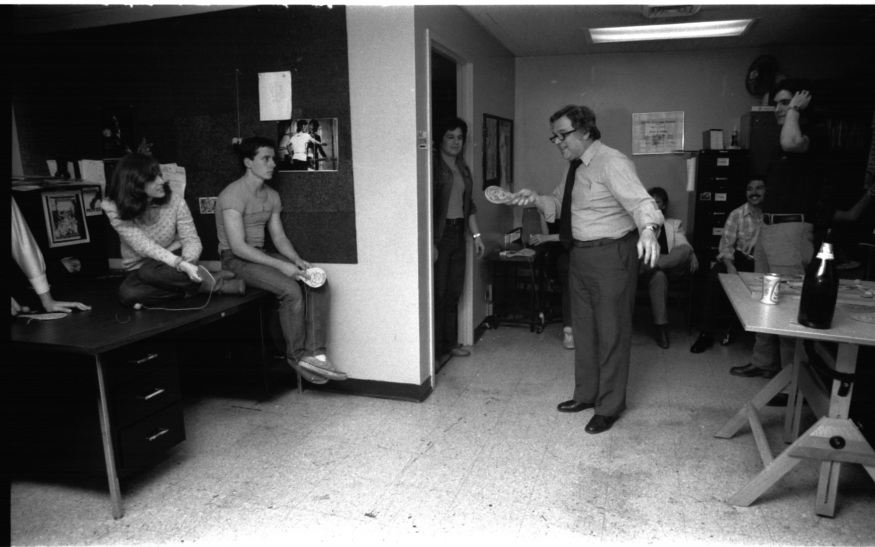 "Jazzy Johnny Romita, on staff Art Director, perhaps the greatest penciler/inker who ever took a magnifying glass to a page and generally regarded as the nicest guy in comics-- cannot seem to see the ball for very long. His son, John ""JR-JR"" Jr., looks on from the doorway, with familial affection."